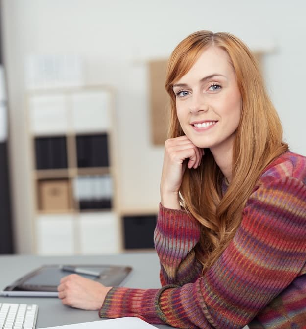 Woman Smiling At Desk Whilst Viewing Customer Documents With Business Central In The Cloud